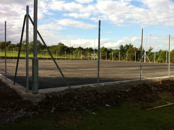 The first layer of tarmac is down and the slots for the netball posts are in.